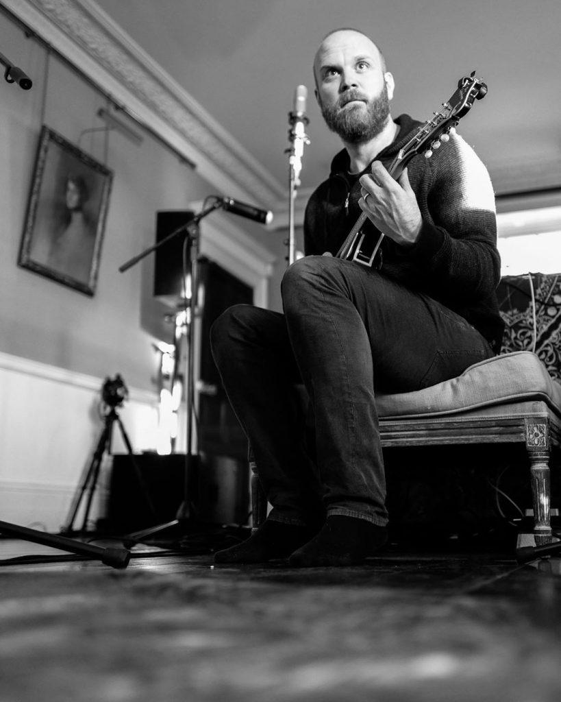 Will Champion com um violão. (Imagem: Guy Berryman/Reprodução/Instagram)