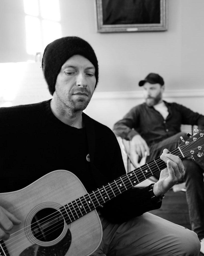 Chris Martin, ao violão, e Jonny Buckland, ao fundo. (Imagem: Guy Berryman/Reprodução/Instagram)