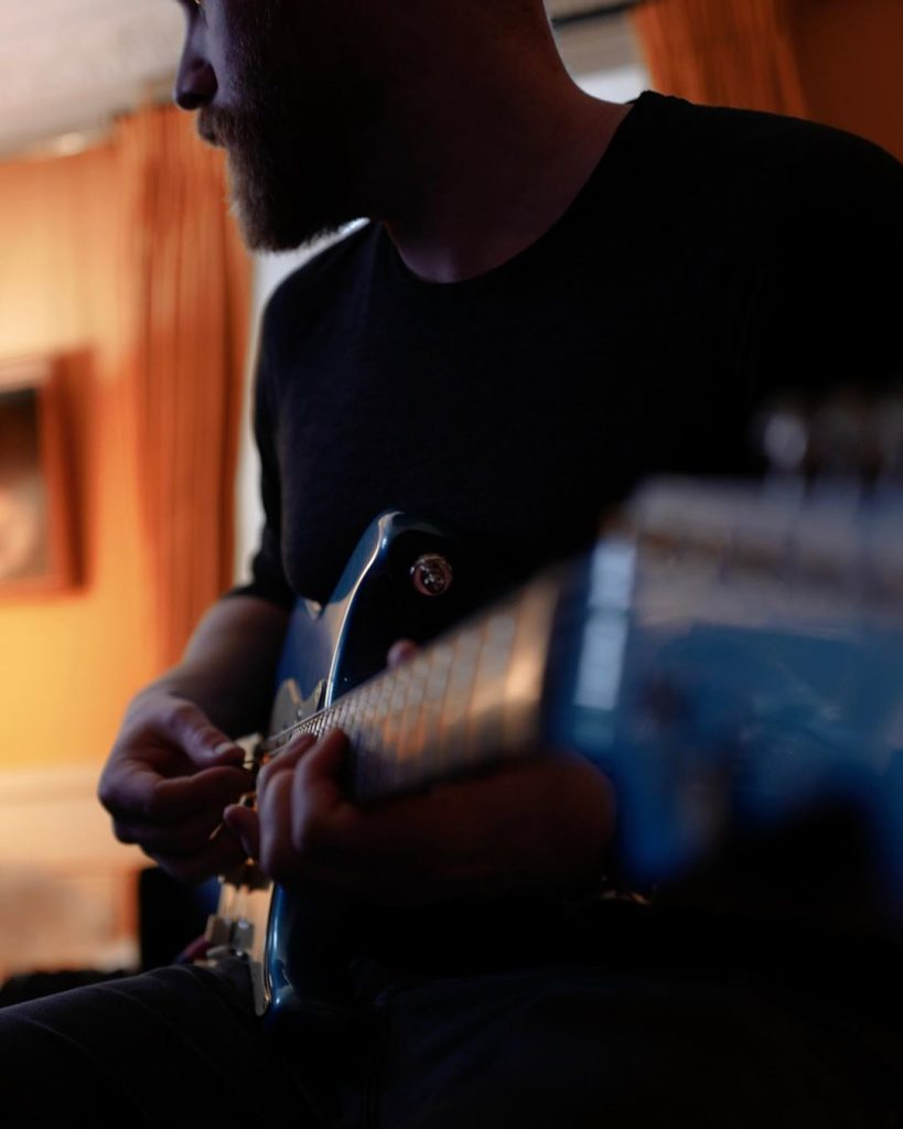 Em plano detalhe, Jonny Buckland dedilha a guitarra. (Imagem: Guy Berryman/Reprodução/Instagram)